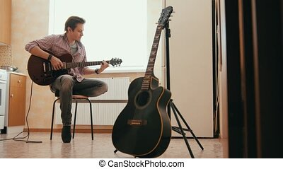 Young man musician composes music on the guitar and plays in...