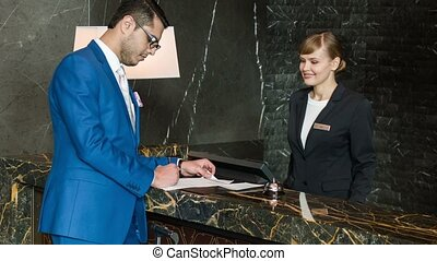Check into hotel. Up-and-coming businessman filling up a form and getting the key to a hotel room at the reception desk