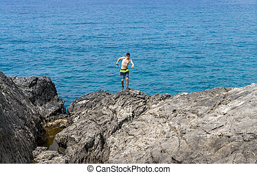 young man on a cliff getting out of balance