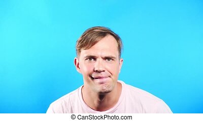 Young man on a colored blue background. portrait. emotions...