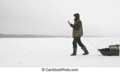 Young man on a frozen lake with a phone looking for the desired route. He pulls on his sleigh things