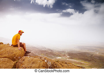 Young man on a rock in the mountains. View of the valley. Lifestyle
