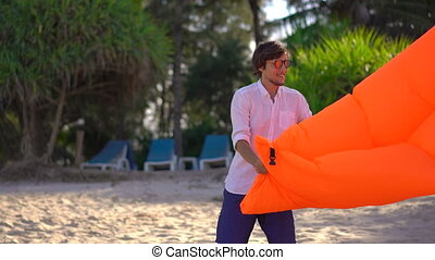 Young man on a tropical beach inflates an inflatable sofa. Summer vacation concept