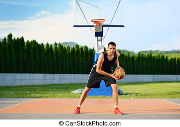 Young man on basketball court dribbling with ball.