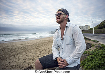 Young man on beach smiling