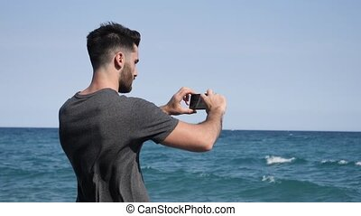 Young man on beach using cell phone to film the sea - Young...