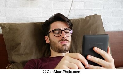 Young man on bed reading with ebook reader - Handsome young...