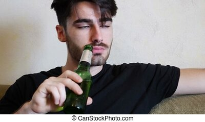 Young man on couch drinking beer and eating - Young...
