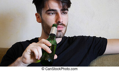 Young man on couch drinking beer