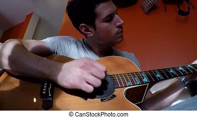Young man on couch playing guitar at home - Young handsome...