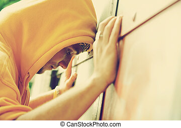 Young man on graffiti grunge wall - Young man in hooded ...