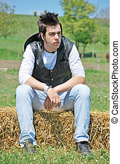 young man on hay bale - young attractive man posing on hay ...