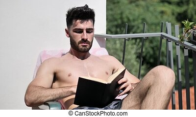 Young Man on Lounge Chair Reading Book - Shirtless Young Man...