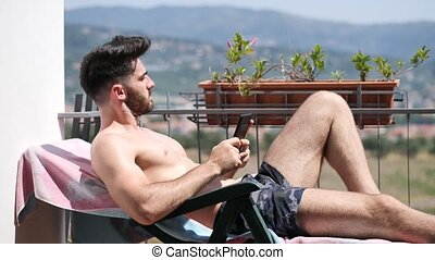 Young Man on Lounge Chair Reading Ebook - Shirtless Young...