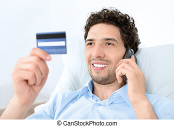 Young man on mobile with credit card