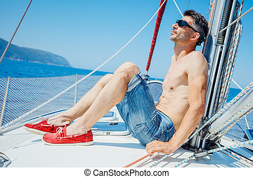 Young man on sailing yacht - Young man relaxing on sailing...