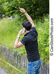 Young man on side of a road, calling and waiting for taxi