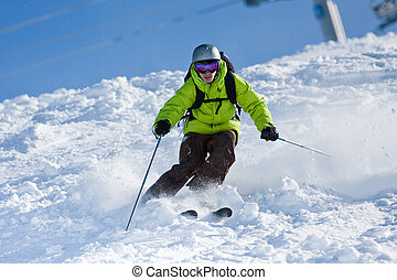 Off-piste skiing - Young man on skis out of slopes....