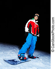 Young man on snowboard at night