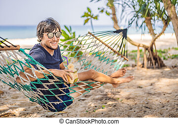 Young man on the beach in a hammock with a drink