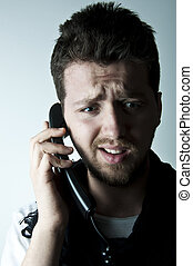 Young man on the phone - Young man talking on a wired phone