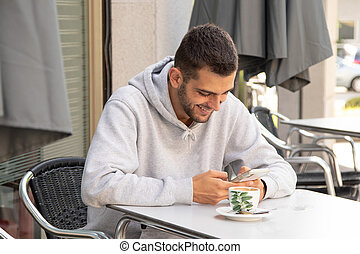 young man on the terrace with mobile phone drinking coffee