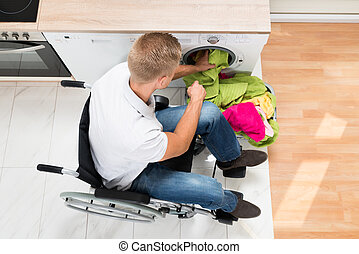 Man On Wheelchair Putting Laundry Into The Washing Machine -...