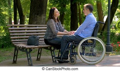 Young man on wheelchair talking with his wife in park