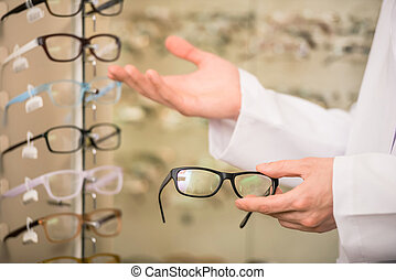 Young man (only hands) at optician with glasses is showing a...