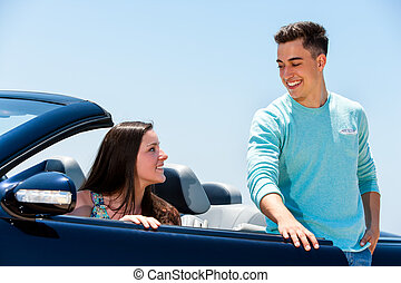 Young man opening car door to woman.