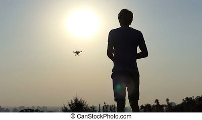 Young man operates his modern drone with panel at sunset in slo-mo