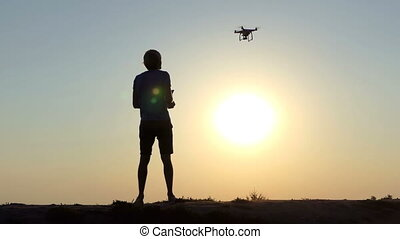Young man operates the flight of a flying drone in Kiev in slo-mo