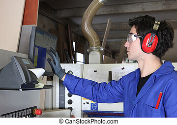 Young man operating factory machinery