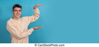 young man or teenager boy pointing out size or growth
