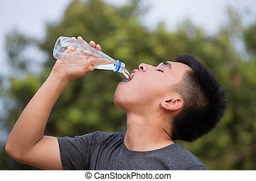 young man or teenager drinking water from bottle