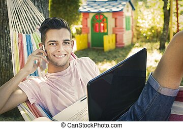 young man or teenager with the laptop in the hammock at sunset summer