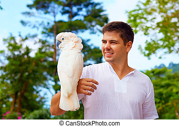 young man, ornithologist holding gorgeous cockatoo parrot