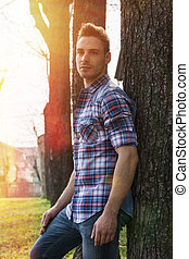 Young man outdoors against a tree, at sunset
