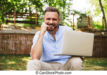 Young man outdoors using laptop computer looking camera.