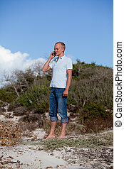 young man outside in summer on beach with mobile phone