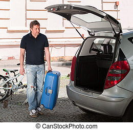 young man packing suitcases in the trunk of a car