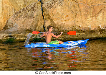 Young Man Paddling Blue Kayak on Beautiful River or Lake under High Rock in the Evening