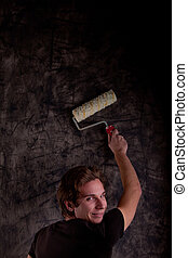young man painting a black wall
