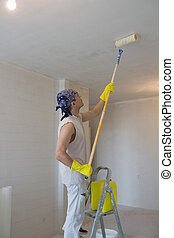 Young man painting ceiling with painting roller
