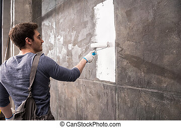 young man painting wall, renovation home concept
