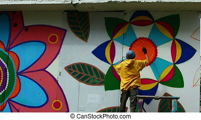 Young man paints wall in park