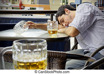 Young man passed out drunk with beer bocks on the glass table of an outdoor terrace: perfect for alcoholism, student hazing, beer binging and other related concepts.