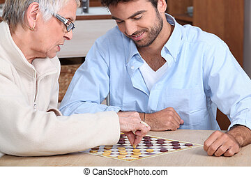 Young man paying game with old lady