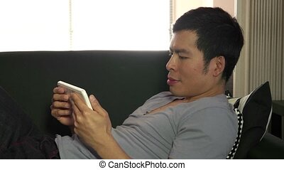 Young Man People Relaxing With iPad - Asian man touching...