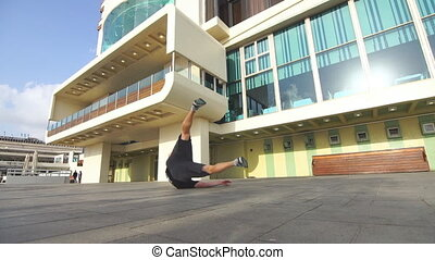 Young man performing flips and doing one arm handstand in the city street at sunny day. Guy showing acrobatic stunts outdoor. Concept of urban sportive lifestyle. Low angle view Close up Slow motion